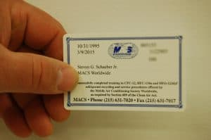 Hand holding a 609 Certification Completion card