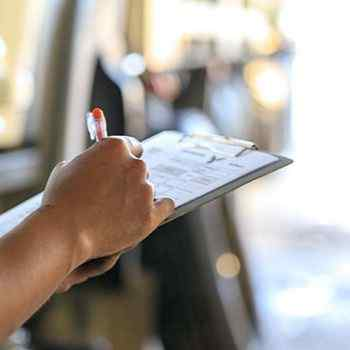 Person's right hand writing on paper on clipboard