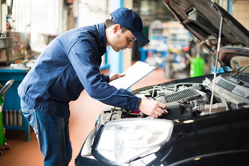 Auto tech inspecting car A/C unit